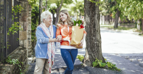 elderly woman walking with younger female